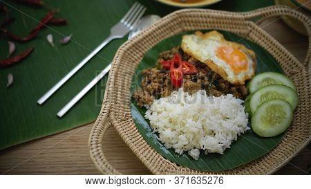 Stir Fried Minced Pork With Basil (pad Ka Prao), Rice Fried Egg Serving On Wicker Plate And Silverwa
