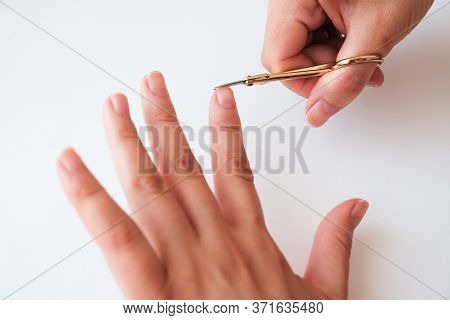 Woman Hands Using A Small Scissors To Cut Her Fingernails On A White Background. View From Above. Ma