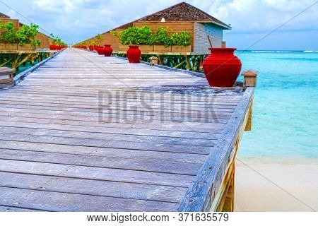 Water Villas, Bungalows And Wooden Bridge At Tropical Beach In The Maldives At Summer Day.tourism Co