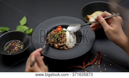 Female Eating Stir Fried Minced Pork With Basil (pad Ka Prao) On Black Table In Thai Restaurant