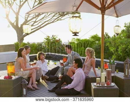 Friends sitting on porch Drinking and socialising under umbrella