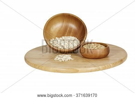 Rolled Oats With Oat Groats In Wooden Bowls On A Bamboo Cutting Board Isolated On White