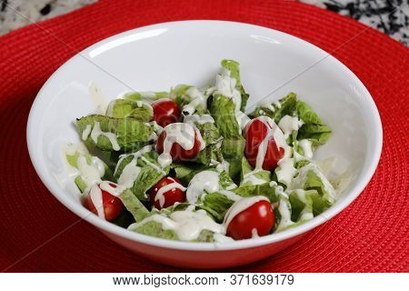 Salad Of Freckles Lettuce, Red Grape Tomatoes And Creamy Ranch Dressing In A White Bowl On A Red Pla