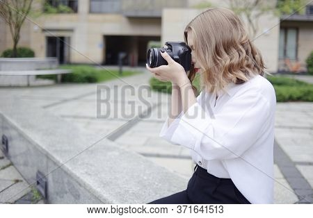A Beautiful Girl Looks In The Viewfinder In The Camera, Takes Pictures. Blonde Learns To Photograph