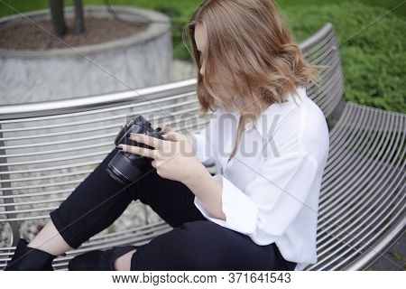 Girl Photographer Is Trying To Figure Out The Settings Of The Camera, Model Looks At Screen Of A Slr
