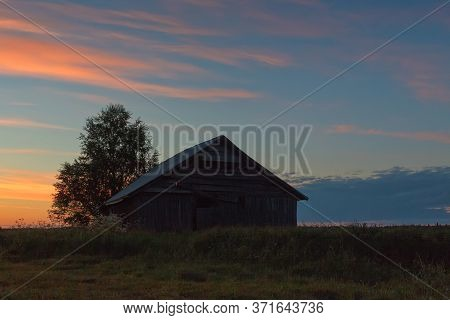 An Old Barn House Against A Beautiful Midsummer Sunset At The Rural Finland.