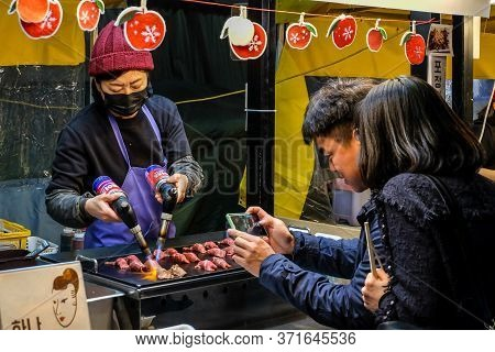 Daegu , South Korea, April 4, 2019: Tourist Taking Picture While Chef Burn A Slice Of Wagyu Beef Wit