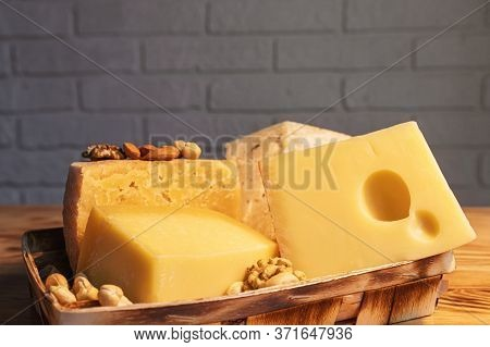 A Variety Of Aged Cheeses In A Substrate On A Wooden Table Against A Brick Wall.