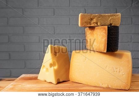 Pyramid Of Various Cheeses On A Wooden Board Against A Brick Wall.