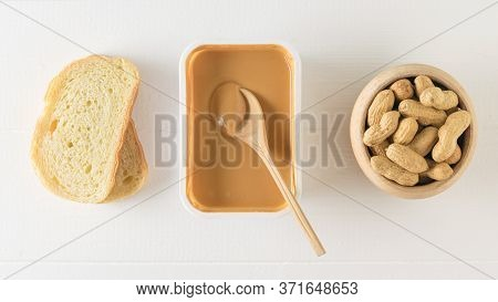 Peanut Paste With A Wooden Spoon, Bread And Peanuts On A White Table. The View From The Top.
