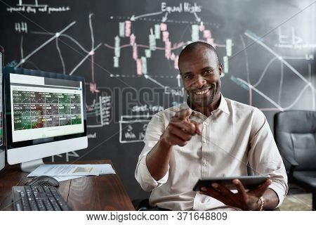 Cheerful African American Male Trader Sitting By Desk, Pointing At Camera And Studying Analytical Re