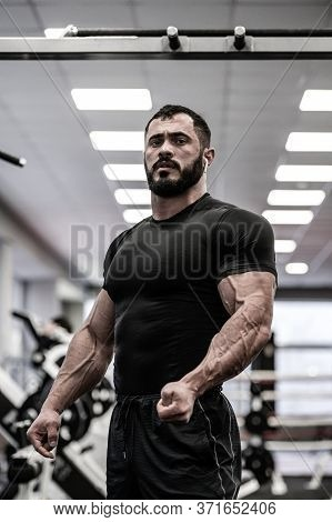 Young Bearded Athlete In Black Jersey With Strong Muscle An Vein In Gym During Posing