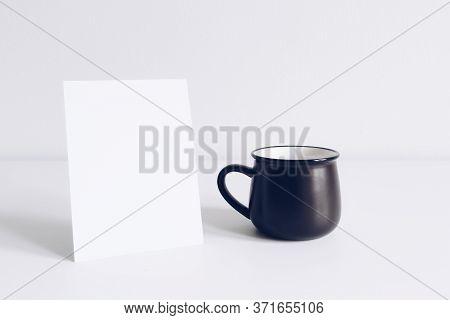Enamel Black Mug And Vertical Postcard On White Table Background Mockup. Boho Style Classic Stock Ph