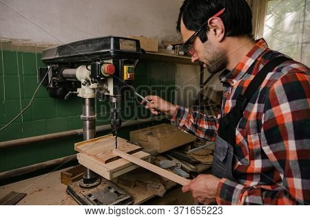 Working Process In The Carpentry Workshop.a Man In Overalls Uses Sthicknessing Planer Machine In A C