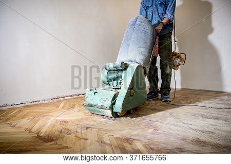 Sanding Hardwood Floor With The Grinding Machine. Repair In The Apartment.