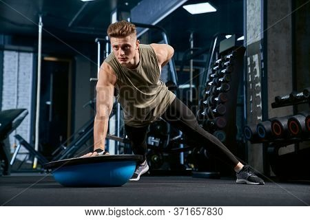 Front View Of Muscular Handsome Man Doing Push Ups On One Hand On Floor Using Balance Half Ball. Clo