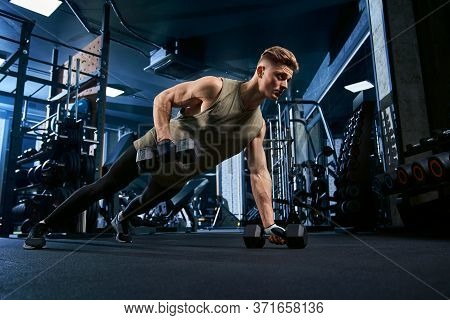 Muscular Caucasian Man Training On Floor Using Dumbbells In Sports Club. Close Up Of Young Sportsman