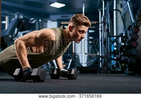 Crop Of Muscular Caucasian Man Training On Floor Using Dumbbels In Sports Club. Close Up Of Young Sp