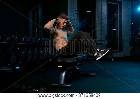 Muscular Caucasian Man Training Abs On Bench In Sports Club. Side View Of Handsome Young Sportsman B