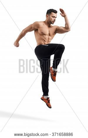 Side View Of Shirtless Caucasian Bodybuilder Jumping In Place. Muscular Man With Perfect Tensed Body