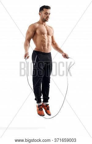 Side View Of Shirtless Caucasian Bodybuilder Jumping In Place Using Rope, Looking Down. Muscular Man
