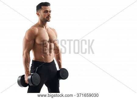 Portrait Of Shirtless Tensed Male Bodybuilder Holding Dumbbells In Arms, Looking Straight. Man With