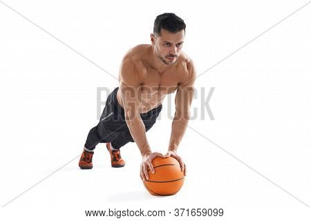 Close Up Of Muscular Shirtless Caucasian Man Training On Floor Using Basketball, Isolated On White S