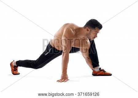 Muscular Handsome Shirtless Man Stretching Legs On Floor Isolated On White Background. Front View Of