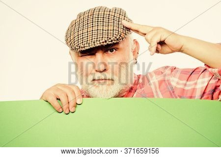Senior Bearded Man Peek Out Of Banner Place Announcement. Pensioner Grandfather In Vintage Hat Hold