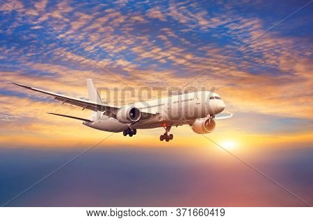 Landing Plane On A Background Of Sunset Sky And Low Clouds Of Fog