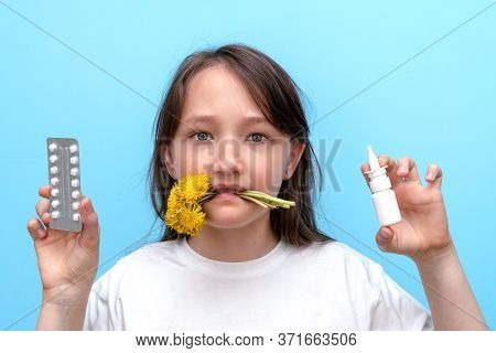 Portrait Of A Child Girl With Flowers In Her Teeth And Anti-allergic Pills And Spray In Her Hands On