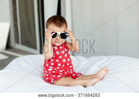 Adorable Baby Girl Wearing Red Dress And Sunglasses On Independence Day On 4th Of July, Childhood An