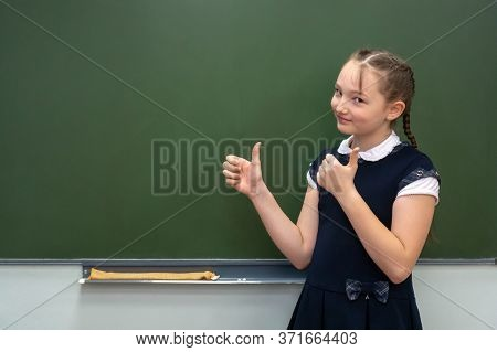 Back To School Concept. Happy Schoolgirl With Backpack At The Black Chalkboard In Classroom. Shows A