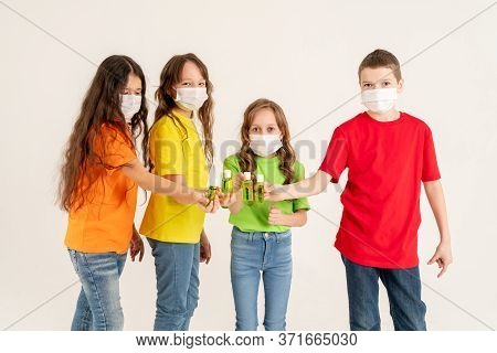 A Group Of Schoolchildren In Bright T-shirts And Medical Masks Are Holding Disinfectants. Stay Home