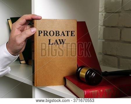 Lawyer Takes A Book Probate Law From A Shelf.