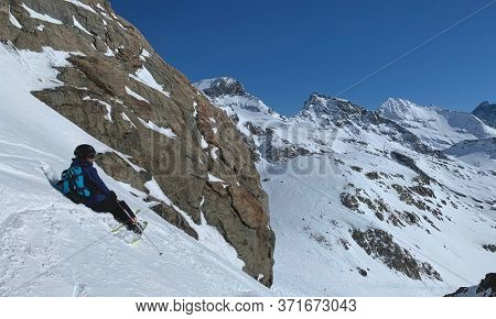 Young skier takes a rest during a freeride excursion in high mountain. Gressoney, Aosta, Italy