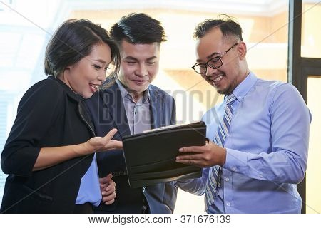 Group Of Three Brand Managers Standing Together Working On Business Plan Looking At Digital Tablet S