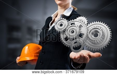 Businesswoman Holds In Palm 3d Gears Mechanism. Woman In Business Suit With Orange Safety Helmet. Co