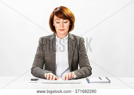 Business Woman Typing On Computer Keyboard. Concentrated Accountant Sitting At Desk On White Wall Ba