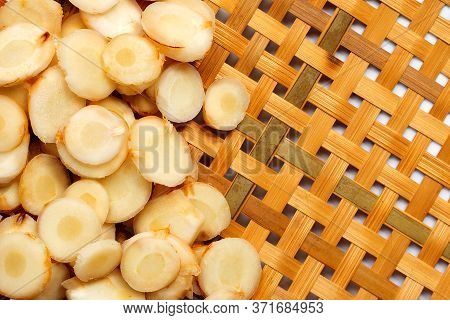 Fresh Galangal Slices On Wooden Bamboo Threshing Basket Background. Top View