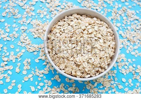 Oat Flakes In Bowl On Blue Background. Healthy Food Concept
