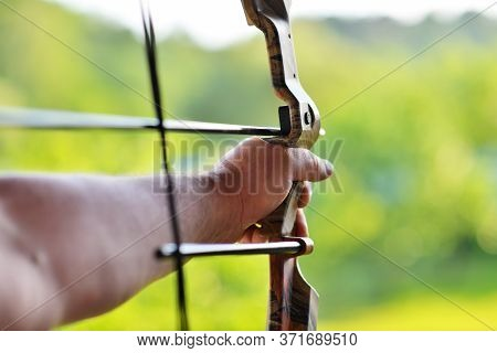 Man's Hand Over Blur Background Of Archery With A Bow In The Foreground During An Archery Competitio