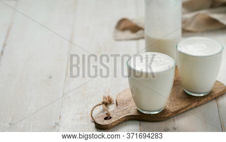 Kefir, Buttermilk Or Yogurt With Probiotics.yogurt In Glass On White Wooden Background.probiotic Col