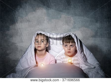 Scared Children With Flashlights Lying In Bed. Little Sister And Brother Hiding Under Blanket Togeth
