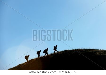 Four mountaineers ascending a grassy knoll in the Oza Valley, Pyrenees, Huesca provonce, Aragon in Spain.