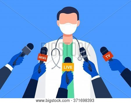 Live Report, Live News Concept. A Male Medical Worker Giving An Interview. Many Hands Of Journalists