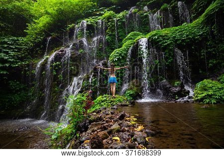 Travel Lifestyle. Young Traveler Woman Wearing Bikini At Waterfall In Tropical Forest. Excited Woman