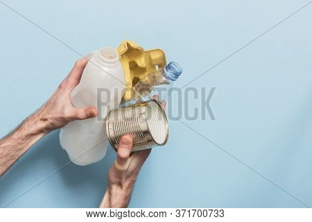 Hand Holding Recycling Rubbish Against A Blue Background