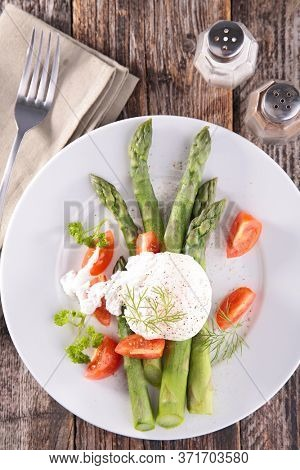 asparagus with poached egg and tomato in plate