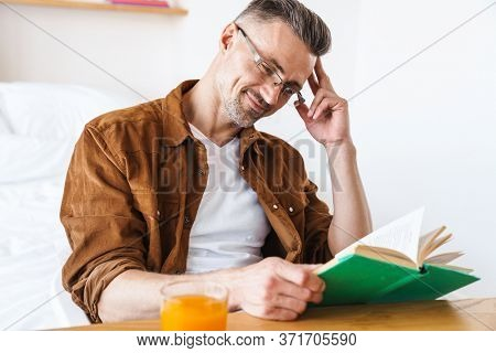 Image of handsome pleased man in eyeglasses reading book and smiling while sitting at table in bedroom
